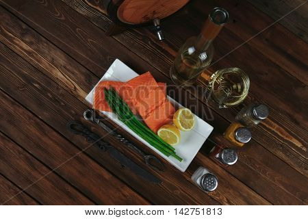 fresh raw salmon fillet served with lemon and white wine in wineglass, wooden barrel, bottle, on white plate over vintage wood table with handmade cutlery knife and fork with empty space background