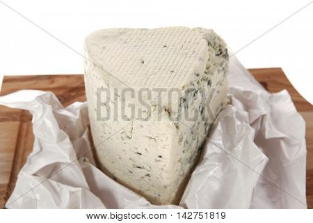 aged italian deli fresh blue stilton cheese served on wooden cutting plate isolated over white background
