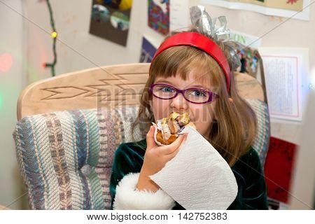 A young girl wearing a green winter dress and red headband with a silver bow and pink glasses eats a huge cinnamon bun for breakfast on Christmas morning.