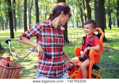 Cheerful young mother in casual outfit looking at her dear son while riding on bike on a sunny day in the park
