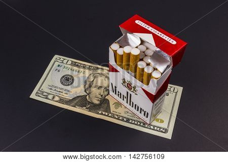 Indianapolis - Circa August 2016: Marlboro Cigarettes and Twenty Dollar Bills Representing the High Costs of Smoking. Marlboro is a product of the Altria Group VII
