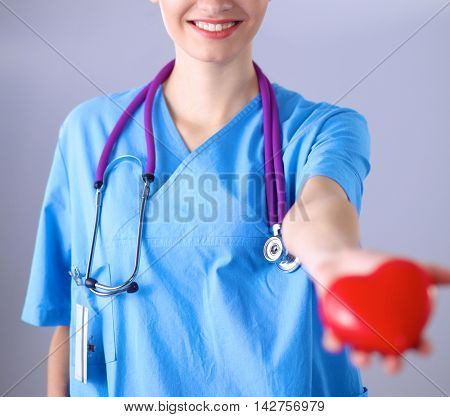 Young woman doctor holding a red heart, standing on gray background