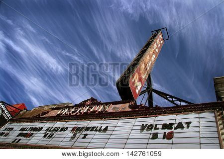 old abandoned theater sign against a blue sky