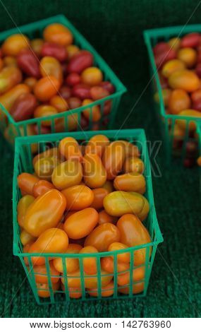 Mix of colorful cherry tomatoes grown and harvested in Southern California and displayed at a farmers market.