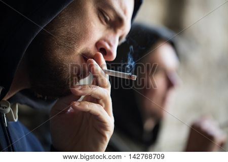 substance abuse, addiction, people and bad habits concept - close up of young man smoking cigarette outdoors