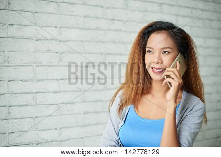 Portrait of lovely Filipino woman having phone talk