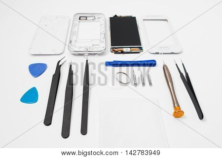 Repairman workplace with phone and special tools. Disassembled smartphone with disassembling instruments and on white background. Electronics repair service, device production concept