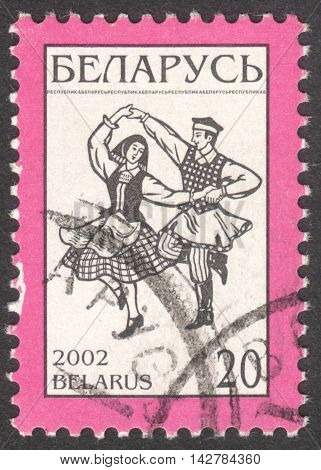 MOSCOW RUSSIA - CIRCA JUNE 2016: a post stamp printed in BELARUS shows dancers in the national costumes circa 2002