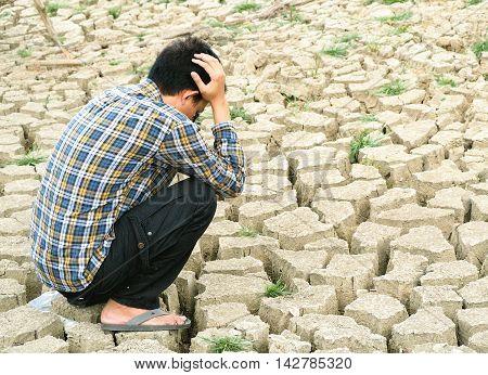 The farmer sitting on mud crack in dry season
