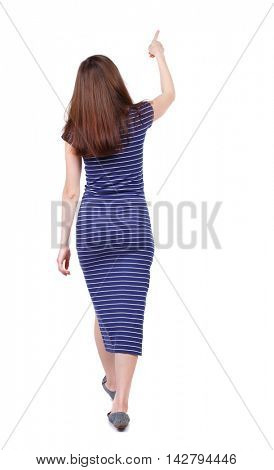 back view of pointing walking  woman. going girl pointing.  backside view of person.  Rear view people collection. Isolated over white background. The brunette in a blue striped dress went off showing