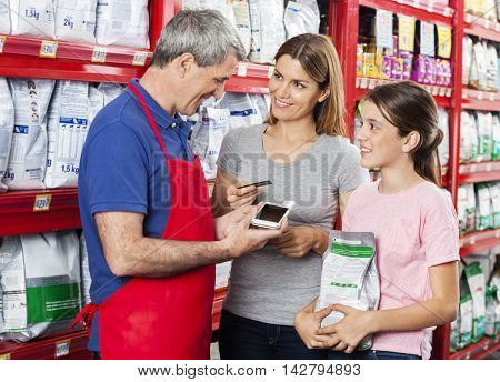 Salesman Accepting Payment From Family In Pet Shop