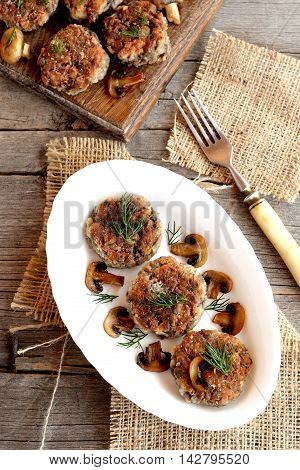 Delicious fried mushroom cutlets on a plate, fork, wooden table. Vegetarian cutlets cooked from mushrooms, onions, eggs, salt, spices and flour. Homemade food