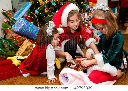 Three sisters in Christmas dresses sit in a circle opening a present. They are in front of a Christmas tree that is fully decorated along with a huge pile of gifts.