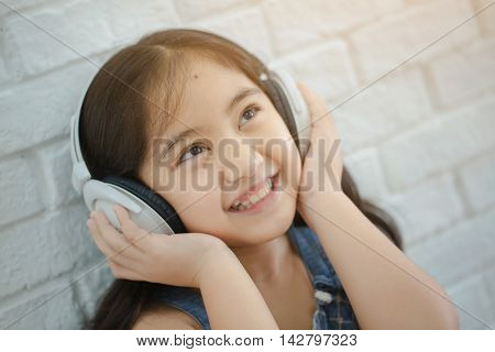 Happy Asian girl listening music by earphone