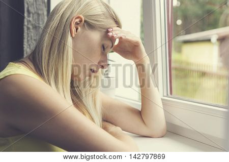 tired depressed woman sitting by the window