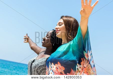 Close up portrait of african girl together with caucasian girlfriend outdoors. Young women standing with eyes closed and open arms enjoying sea breeze.