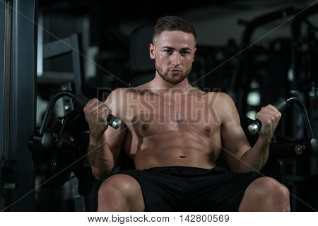 Young Bodybuilder Doing Exercise For Biceps On Machine