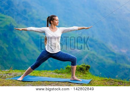 Yoga outdoors - sporty fit woman doing Ashtanga Vinyasa Yoga asana Virabhadrasana 2 Warrior pose posture in mountains