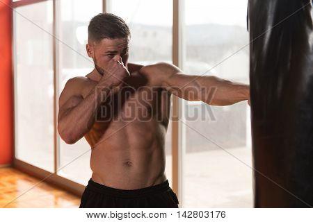 Shirtless Muscular Boxer With Punching Bag In Gym