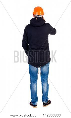 Backview of an engineer in construction helmet stands. Standing young guy. Rear view people collection. backside view of person. Isolated over white background. Engineer in warm clothing standing in a