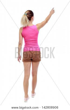 Back view of  pointing woman. beautiful girl. Rear view people collection.  backside view of person.  Isolated over white background. Sport blond in brown shorts goes back frame showing thumb up.
