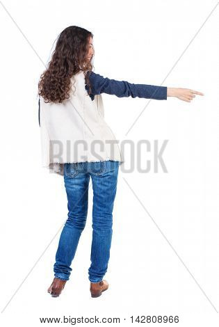 Back view of  pointing woman. beautiful girl. Rear view people collection.  backside view of person.  Isolated over white background. Long-haired girl with curly hair is pointing to the right.