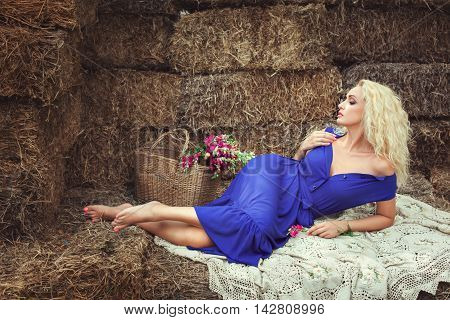 Blonde woman lying on hayloft near a basket with flowers. She expects a man.