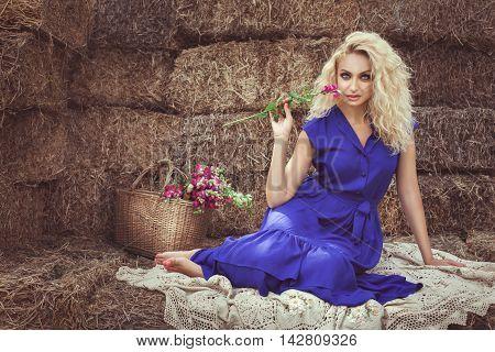 Woman with flower sitting on hayloft she looks flirting.