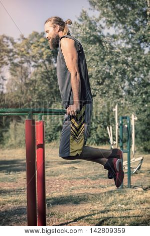 Training outdoors. Man doing biceps and triceps dips training on horizontal bars in the sport park. poster