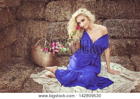 Beautiful woman on hayloft sitting and smiling she flirts.