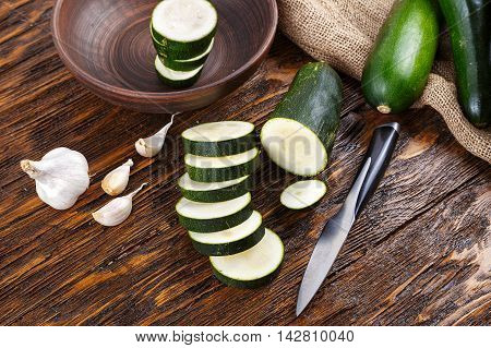 zucchini slices and whole zucchini lying on the board lies next to the garlic knife and napkin of burlap