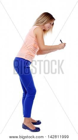 back view of writing beautiful woman. Rear view people collection.  backside view of person. Isolated over white background. The blonde in a pink t-shirt wrote marker.
