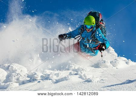 Free-ride skier running downhill in freeze motion of snow powder.