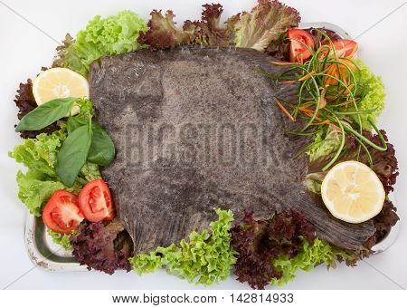 whole prepared turbot with  vegetables on plate