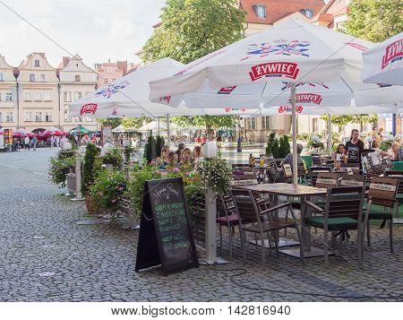 JELENIA GORA POLAND - AUGUST 13 2016: Tourists At A Cafe At Townhall Square in Jelenia Gora Poland