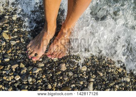 Young and beautiful female bare feet with red painted nails or pedicure standing on a beach, waves bathes her feet. Summer vacation concept.
