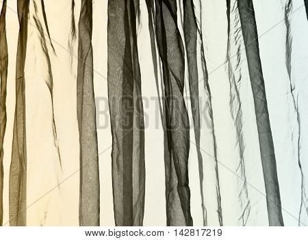 Voile crumbled folded curtain background in yellow, brown, green dark colours