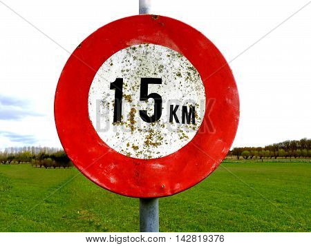 old dirty 15 km per hour speed sign with meadow background