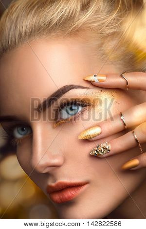 Beauty blonde model sexy girl face. Beautiful Fashion woman with perfect golden makeup, nail art manicure and accessories. Holiday Fashion art portrait
