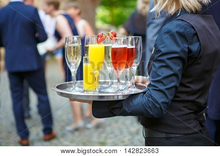 A waiter or waitress with a tray of glasses of champagne, delicious punch and glasses of orange juice at the wedding reception. Glasses with alcohol and different drinks