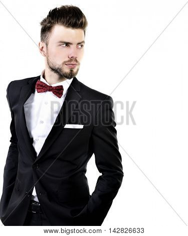 Portrait of handsome stylish man in elegant black suit and red bow-tie isolated on white background