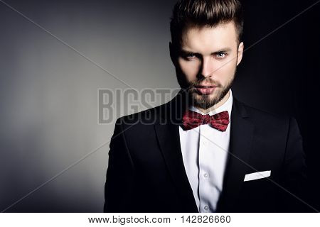 Portrait of handsome stylish man in elegant black suit and red bow-tie over gray background