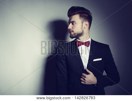 Portrait of handsome stylish man in elegant black suit and red bow-tie looking right at copy space over gray background, image toned