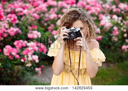 Young beautiful photographer in yellow dress walking around city.