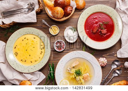 Assorted soups on the table, overhead view. Ukrainian and Russian National vegetable soup - red borsch. Fish soup, Pumpkin soup.
