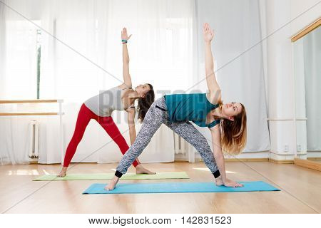 Portrait of two beautiful girls showing ashtanga vinyasa triangle yoga pose