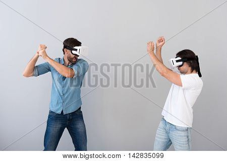 Involved in game. Pleasant involved young men using virtual reality device and playing game while standing isolated on grey background