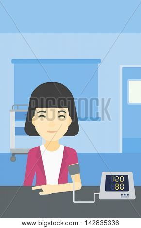 Asian woman checking blood pressure with digital blood pressure meter. Woman taking care of her health and measuring blood pressure in hospital room. Vector flat design illustration. Vertical layout.