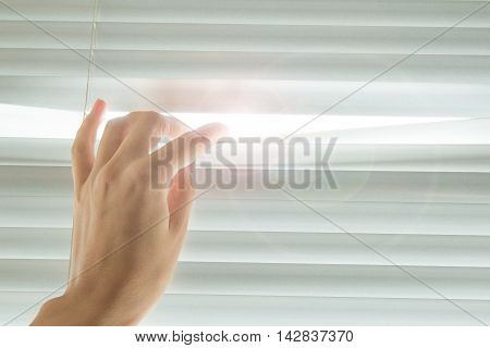 Woman's hand opens the blinds in sunny day