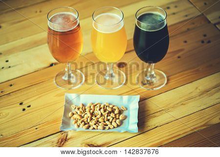 Beautiful Background Of The Oktoberfest. Glasses Of Cold Fresh White, Light And Dark Beer With Peanu